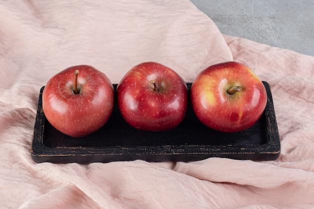 Holzplatte mit drei äpfeln auf textiloberfläche