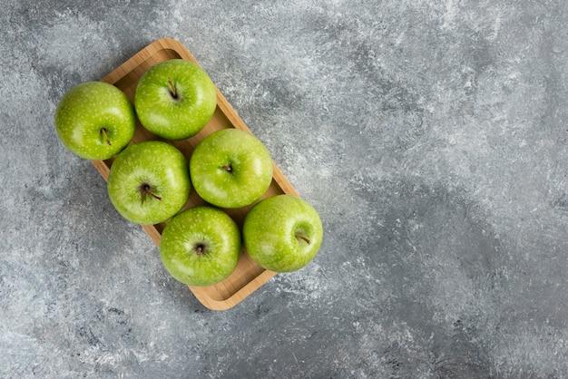 Holzplatte mit glänzenden grünen äpfeln auf marmortisch.