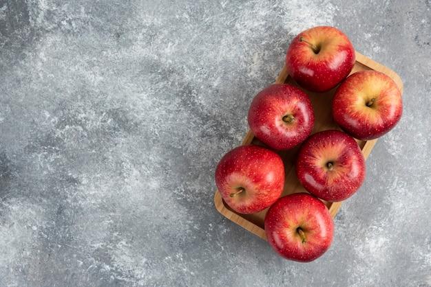 Holzplatte mit glänzenden roten äpfeln auf marmortisch.