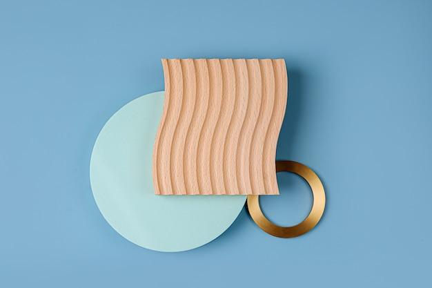Holzplatte mit wellen und runden geometrischen formen auf blauem grund. stilvoller hintergrund mit goldenen elementen
