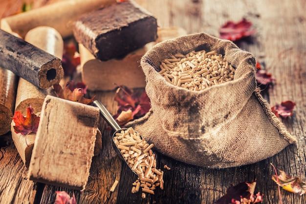 Holzpresspellets und -briketts aus biomasse mit herbstlaub.
