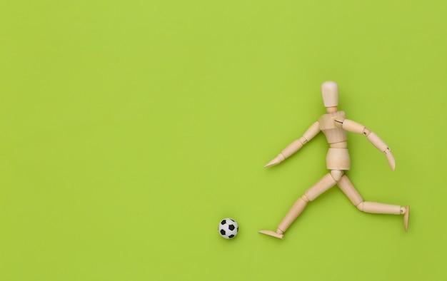 Holzpuppe, die fußball mit einem ball auf grünem hintergrund spielt