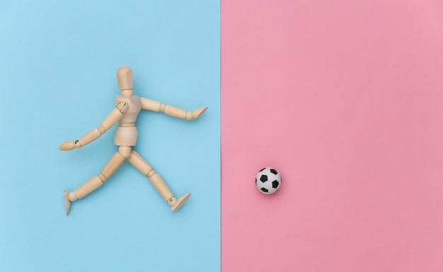 Holzpuppe, die fußball mit einem ball auf rosa blauem hintergrund spielt