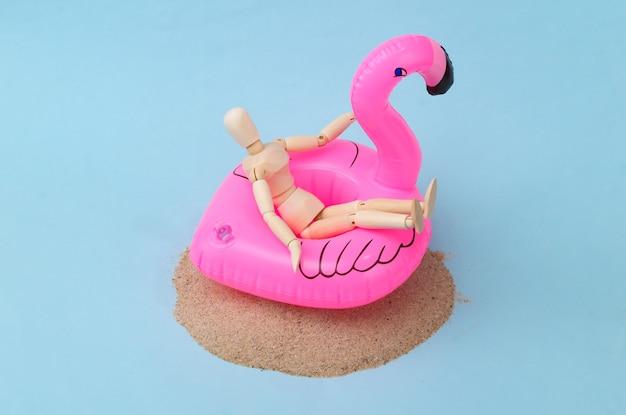 Holzpuppe mit aufblasbarem flamingo auf sandinsel. reisen, strandurlaub konzept