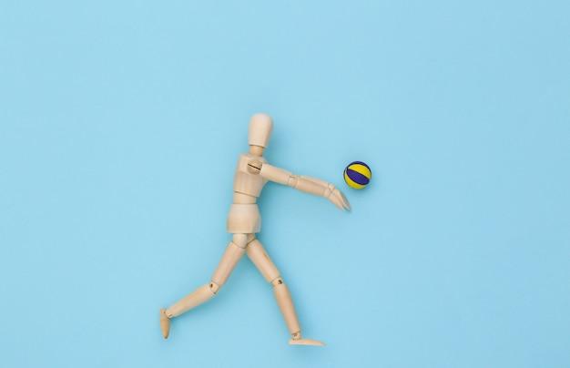 Holzpuppe spielt volleyball mit ball auf blauem hintergrund