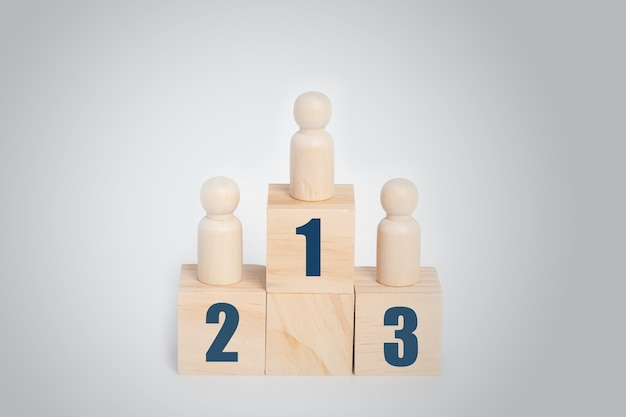 Holzpuppe stehend auf podium 1, 2, 3 von holzbausteinen, geschäftshierarchie, rangfolge.