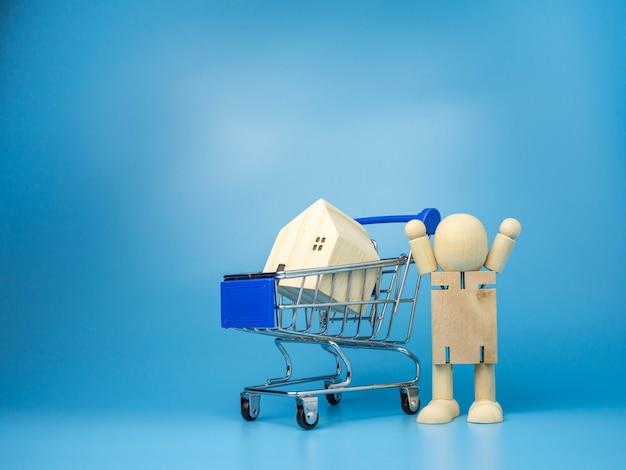 Holzpuppen, die neben dem einkaufswagen stehen mit einem modellholzhaus auf blau