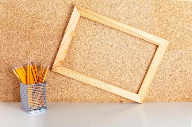 Holzrahmen auf pinnwand und stifte im halter