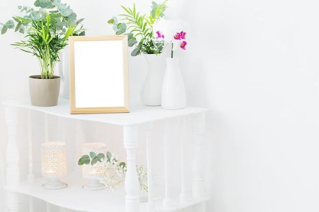 Holzrahmen auf vintage weißem regal mit blumen und pflanzen