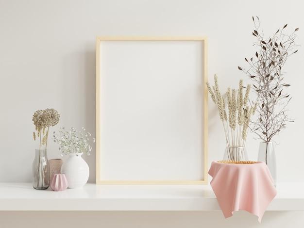 Holzrahmen, der sich auf weißes regal im hellen innenraum mit pflanzen auf dem tisch mit pflanzen in töpfen auf leerer wand stützt.