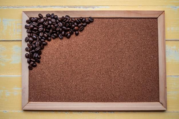 Holzrahmen für text und kaffeebohnen auf einer holzoberfläche.