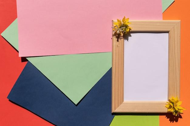 Holzrahmen mit gelben blumen auf geometrischem buntem schattenpapierhintergrund