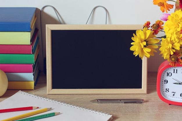 Holzrahmen mit schwarzer leerer hintergrundtafel auf dem tisch schulmodell zurück in die schule 1. september tag des wissenstag des lehrers