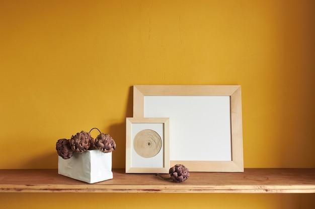 Holzrahmen modell. trockene dekorative artischocken in einer vase auf einem alten holzregal. zusammensetzung auf einer gelben wandfläche