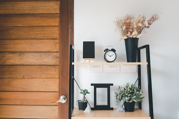 Holzregal mit blumenstrauß der trockenen blume, gras im topf, grün in der vase, alarm, fotorahmen und tafel über weißer wanddekoration im wohnzimmer zu hause