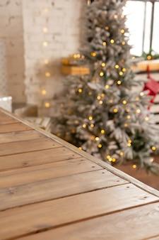 Holzregal vor dem hintergrund einer leuchtenden girlande am weihnachtsbaum platz für ihre produkte