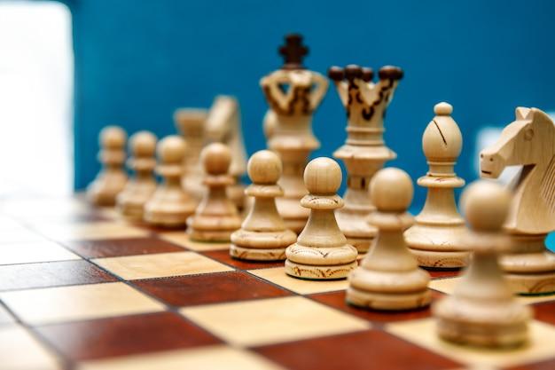 Holzschachfiguren auf dem schachbrett, weiß vor spielbeginn