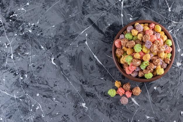 Holzschale der köstlichen bunten popcorns auf marmorhintergrund.