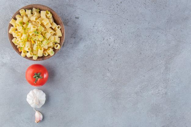 Holzschale der köstlichen gekochten nudeln auf steinhintergrund.