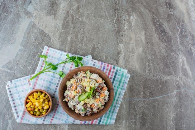 Holzschale des köstlichen russischen salats auf marmoroberfläche.
