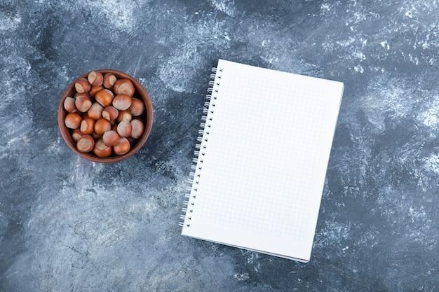 Holzschale mit bio-haselnüssen mit leerem notizbuch.