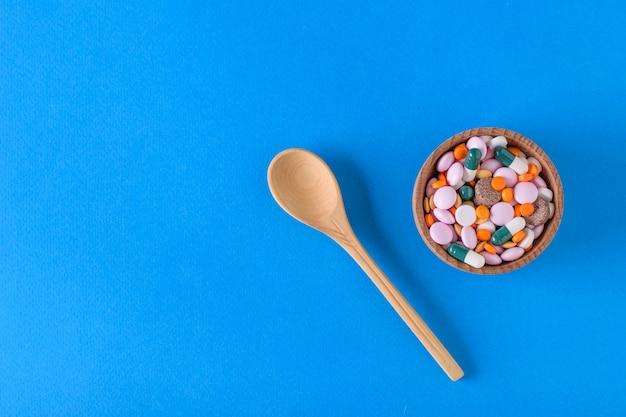 Holzschale mit bunten pillen und holzlöffel auf blauem hintergrund. der blick von oben. das konzept der behandlung und prävention von krankheiten. flach liegen.