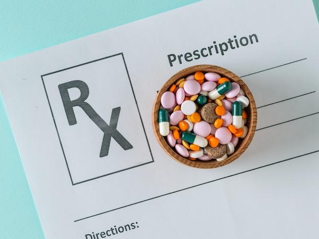 Holzschale mit bunten tabletten auf dem formular mit der ernennung eines arztes gefüllt. der blick von oben. das konzept der behandlung und prävention von krankheiten. flach liegen.