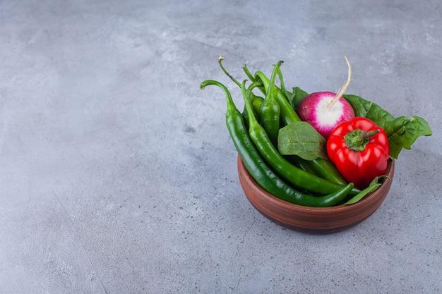 Holzschale mit chili und paprika mit rettich auf blau.