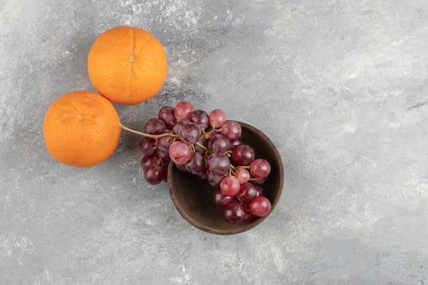 Holzschale mit frischen roten trauben und orangen auf marmoroberfläche.
