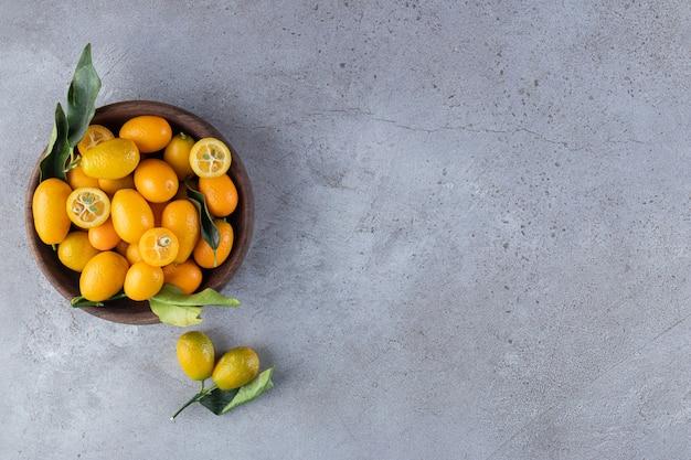 Holzschale mit frischen saftigen kumquats auf steinoberfläche