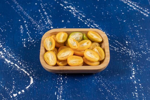Holzschale mit geschnittenen frischen kumquat-früchten auf marmoroberfläche