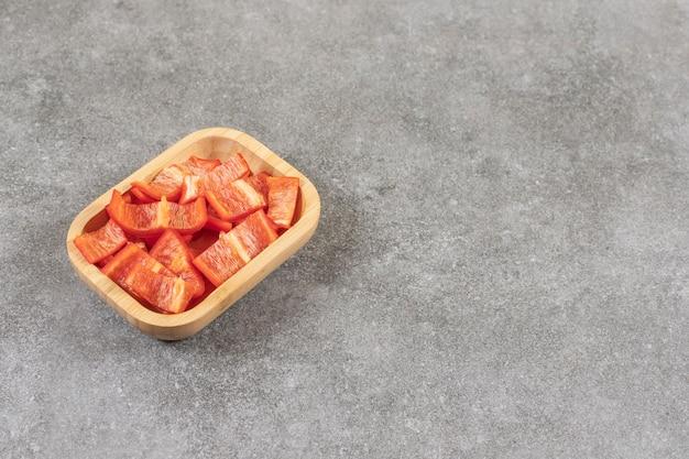 Holzschale mit geschnittenen roten paprikaschoten auf marmoroberfläche.