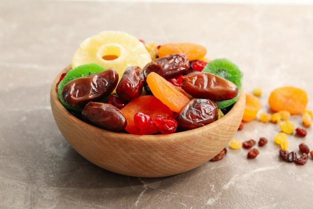 Holzschale mit getrockneten früchten auf grauem tisch