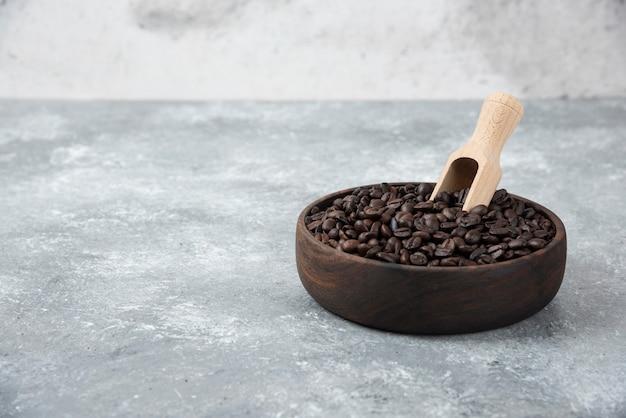 Holzschale mit mittel geröstetem kaffee mit löffel auf marmoroberfläche.