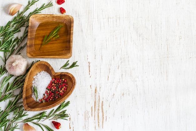 Holzschale mit olivenöl und gewürzen auf weißem hintergrund. draufsicht mit kopienraum.