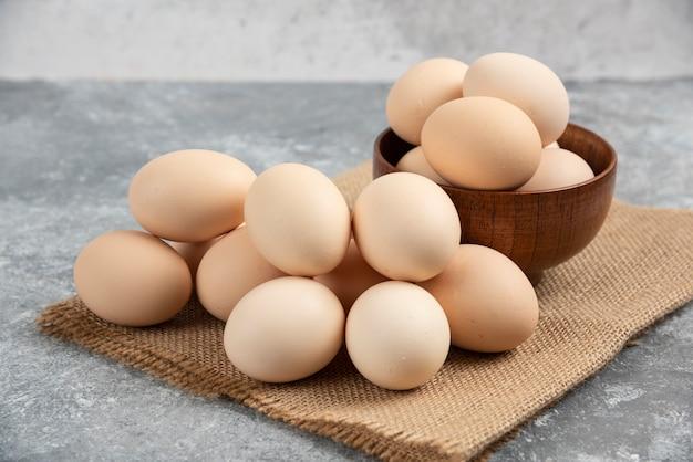 Holzschale mit rohen bio-eiern auf marmoroberfläche.
