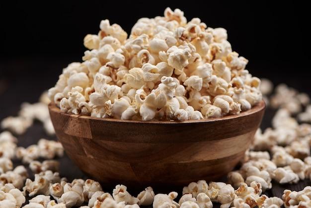 Holzschale mit salzigem popcorn auf einem holztisch. dunkler hintergrund. selektiver fokus.