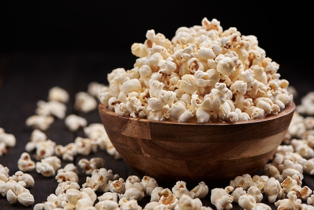 Holzschale mit salzigem popcorn auf einem holztisch. dunkler hintergrund selektiver fokus.