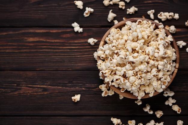 Holzschale mit salzigem popcorn auf einem holztisch.