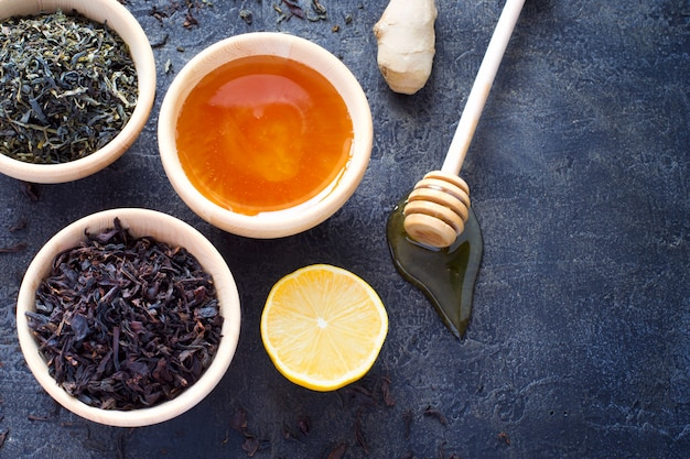 Holzschale mit trockenem tee und frischem honig, zitrone und ingwer