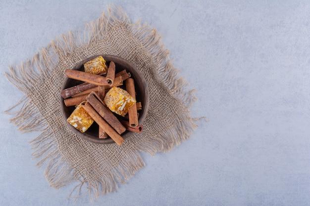 Holzschale mit zimtstangen und nussbonbons auf steintisch.