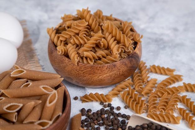 Holzschalen mit ungekochten trockenen italienischen nudeln mit pfefferkörnern. hochwertiges foto