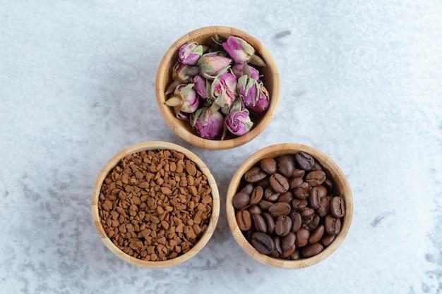 Holzschalen voller aromatischer kaffeebohnen, kaffee und getrockneter rosenblüten. hochwertiges foto
