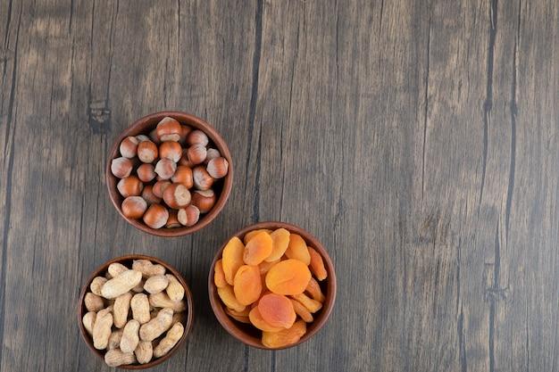 Holzschalen voller gesunder nüsse mit getrockneten aprikosenfrüchten auf holztisch.