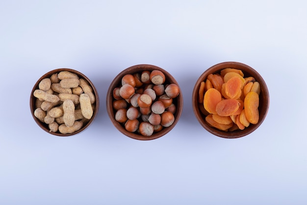 Holzschalen voller ungeschälter erdnüsse, haselnüsse und getrockneter aprikosen auf weiß.