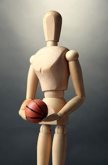 Holzschaufensterpuppe mit basketballball auf grauer wand