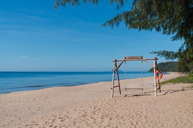 Holzschaukel am sandstrand am strand von ban krut. reiseziel in prachuap khiri khan, thailand. sommerurlaub entspannen. ruhiges wellenmeer.