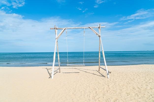 Holzschaukel am strand mit meeresstrand hintergrund