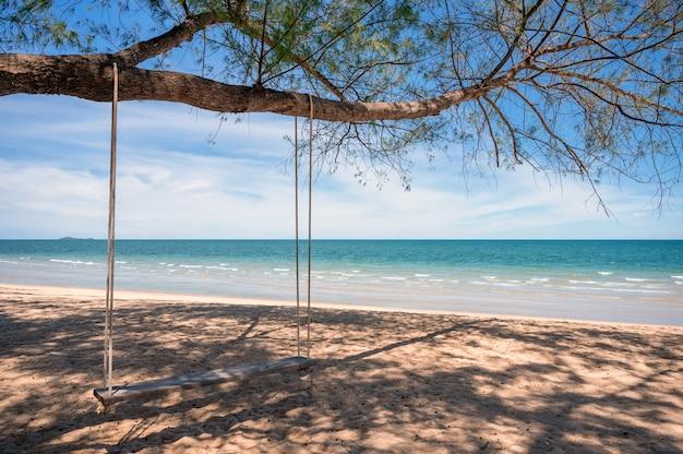 Holzschaukel, die am baum am strand im tropischen meer hängt.