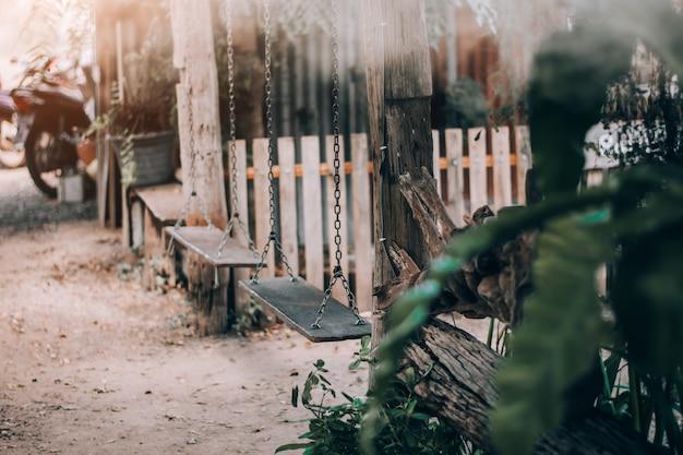Holzschaukel mit blumen im park.